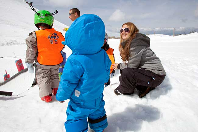 Children enjoying the snow with their parents Sierra Nevada